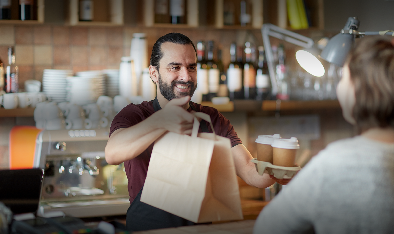 Man serving customer at coffee shop