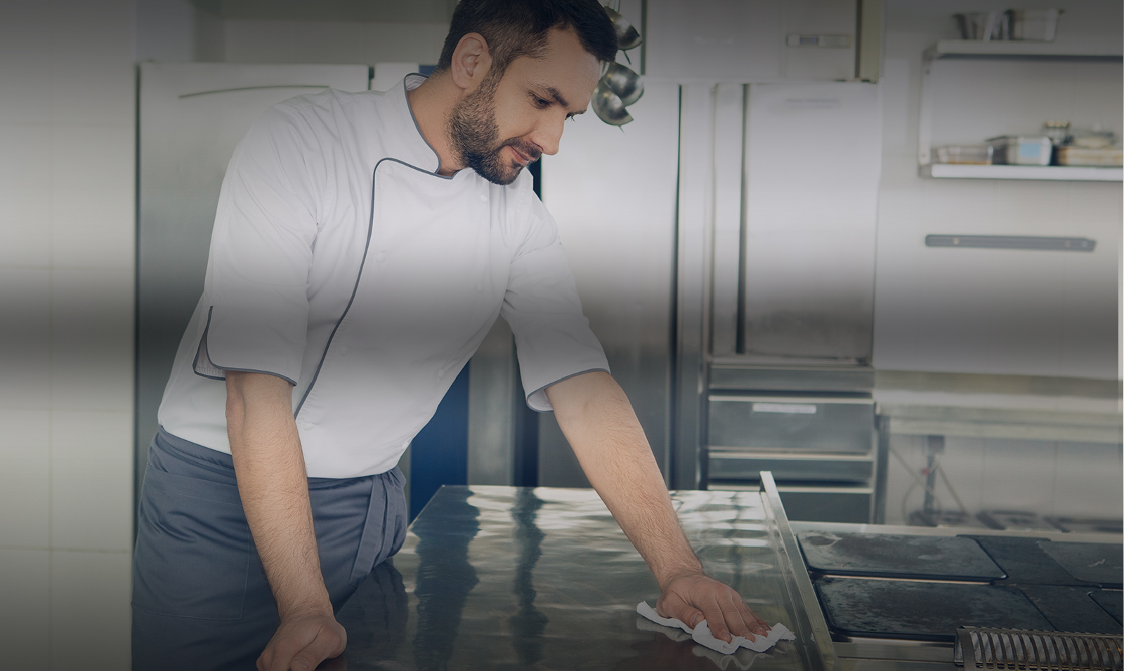 Chef cleaning a work space in the kitchen with a cloth