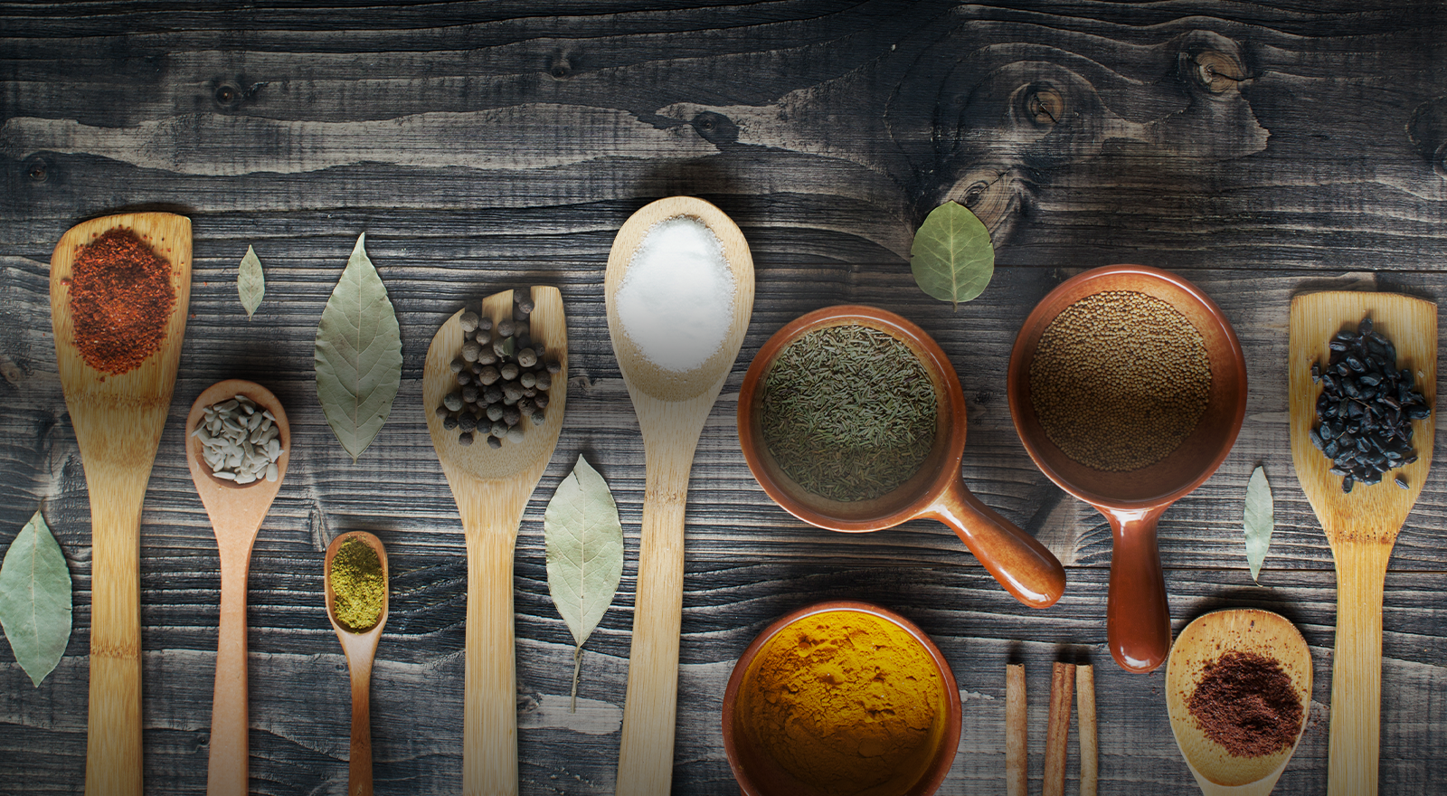 An assortment of spices in measuring cups and on wooden spoons laid out on a wooden board.