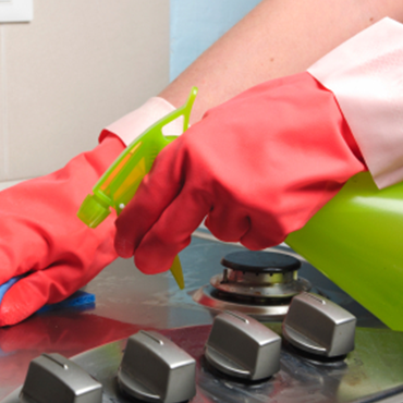 Cleaning stove top range with spray bottle cleaner and latex gloves