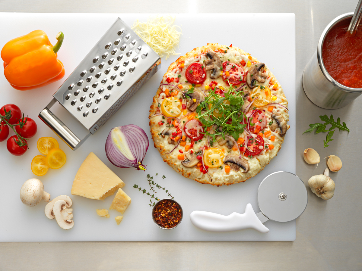 pizza ingredients, utensils, and a pizza