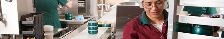 Food worker in commercial kitchen preparing meals for delivery