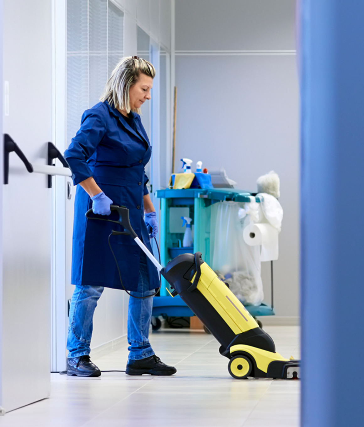 Woman cleaning the floors with a heavy duty vacuum