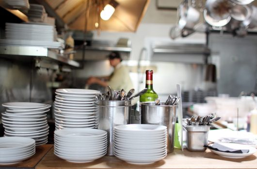 Stacked dishes and flatware in a kitchen ready for meal plating.