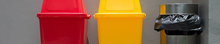 Colorful trash bins and a smoke bin outside a building