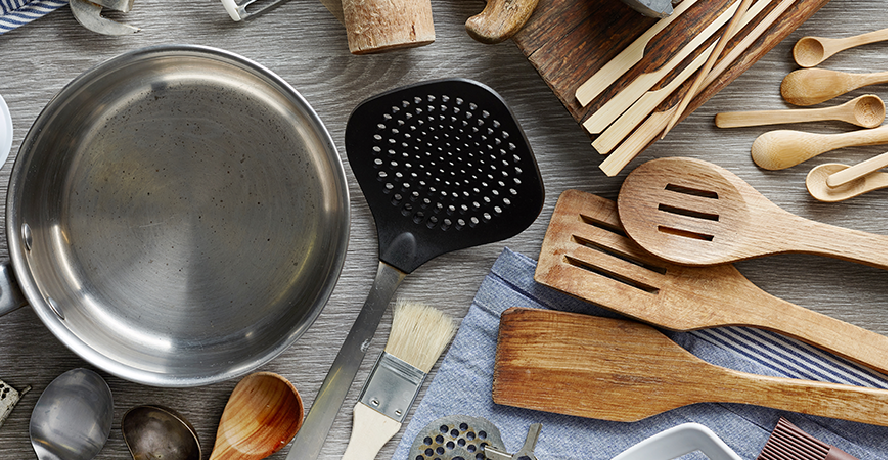 An array of kitchen supplies and cookware; from pots and peelers to ladles and spoons.