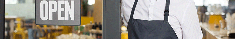A café employee wearing a blue apron