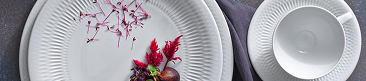 A table spread of dinnerware patterns by Premier Collections